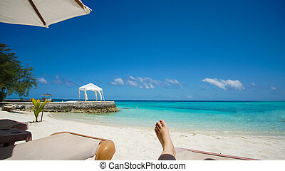 Feet tourist relax at Maldives turquoise sea white sand tropical beach paeadise