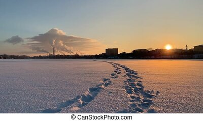 Feet traces with winter industrial landscape over the snow...
