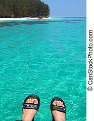 feet up - looking across blue water with feet in the...