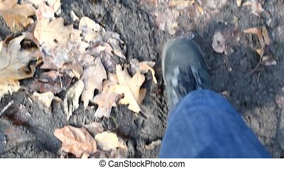 Feet walk on ground with fallen leaves in slomo