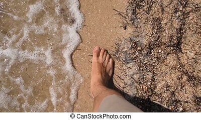 Feet walking barefoot on sandy beach in real time - Point of...
