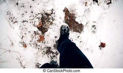 Feet walking slowly on snow in winter