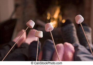 Feet warming at a fireplace with marshmallows on sticks