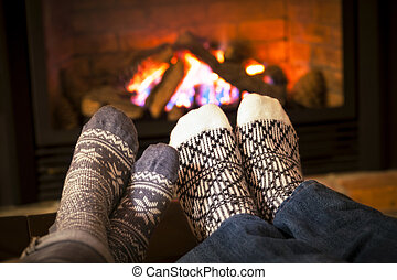 Feet warming by fireplace - Feet in wool socks warming by...