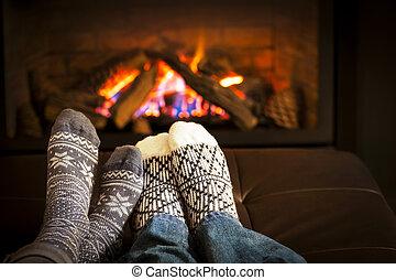 Feet warming by fireplace - Feet in wool socks warming by...