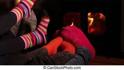 Close Up Of Cosy Family At Home Wearing Socks Warming Feet By Flames Of Wood Burning Stove Fire