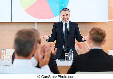 feiern, success., sicher, fälliger mann, in, formalwear, gesturing, und, lächeln, während, machen, darstellung, in, sitzungssaal, mit, leute, klatschende , auf, der, vordergrund