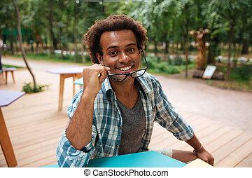 felice, attraente, giovane africano, in, occhiali, seduta, fuori