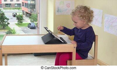 felice, biondo, ragazza, toccante, tavoletta, schermo calcolatore, con, dito
