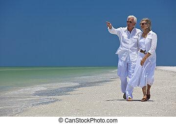 felice, coppie maggiori, camminare, indicando, mare, su, spiaggia tropicale