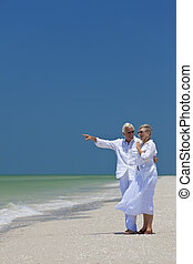 felice, coppie maggiori, indicando, mare, su, spiaggia tropicale