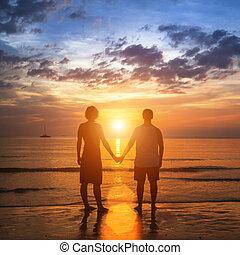 felice, giovane coppia, tenere mani, su, mare, spiaggia, durante, il, bello, sunset.