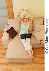 felice, giovane, sedere divano, con, laptop