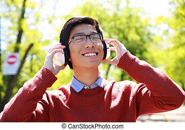 felice, giovane, uomo asiatico, ascoltando musica, parco