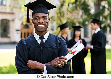 felice, graduate., felice, uomo africano, in, vesti graduazione, presa a terra, diploma, e, sorridente, mentre, suo, amici, standing, in, il, fondo