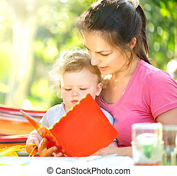 felice, madre, lettura libro, a, lei, poco, bambino, in, soleggiato, parco