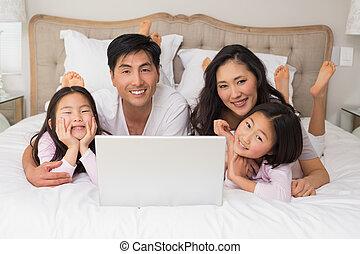 felice, rilassato, famiglia quattro, usando computer portatile, letto