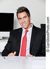 felice, uomo affari, sedendosi scrittorio