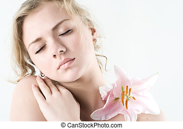 Beautiful young woman with pink lily