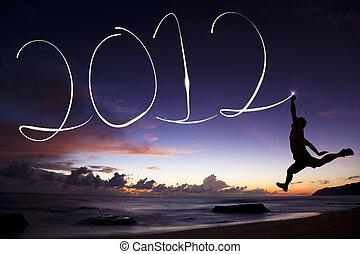 feliz año nuevo, 2012., joven, saltar, y, dibujo, 2012, por, linterna, en el aire, en la playa, antes, salida del sol