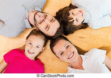 feliz, a, ser, un, family., punta la vista, de, familia feliz, de, cuatro, vinculación, a, uno al otro, cabezas, y, sonriente, mientras, acostado, en, el, h, piso