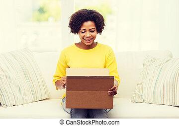 feliz, africano, mujer joven, con, paquete, caja, en casa
