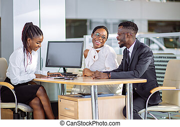 feliz, africano, pareja, con, comerciante, coche que compra, en, automóvil, exposición, o, salón