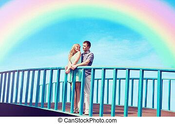 feliz, bastante, pareja joven, enamorado, en, el, puente, encima, cielo azul, y, colorido, rainbow., día de valentín, y, relaciones, concepto