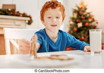 feliz, cacheados, haired, criança, tocando, com, homem bolo gengibre