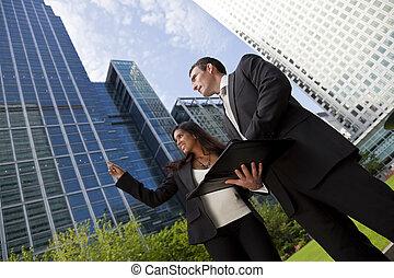 feliz, carrera mezclada, hombre de negocios, y, mujer de negocios, equipo, en la ciudad