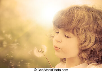 feliz, criança, soprando, dandelion