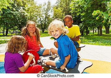 feliz, crianças, sentando, ligado, pátio recreio, carrossel