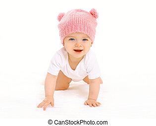 feliz, cute, bebê sorridente, em, tricotado, cor-de-rosa, chapéu, anda de gatas, branco, fundo
