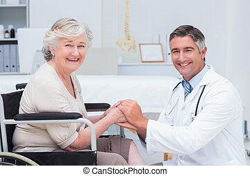 feliz, doutor, segurando, sênior, pacientes, mãos