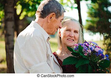 feliz, e, muito, antigas, par, sorrindo, em, um, parque, ligado, um, ensolarado, day.