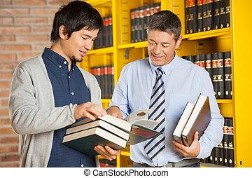 feliz, estudante masculino, segurando, livros, enquanto, discutir, com, bibliotecário, em, faculdade, biblioteca