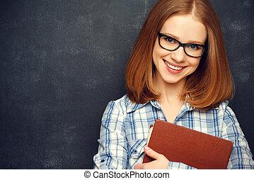 feliz, estudante menina, com, óculos, e, livro, de, quadro-negro