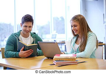 feliz, estudantes, com, laptop, e, livros, em, biblioteca