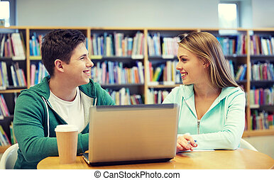 feliz, estudantes, com, laptop, em, biblioteca