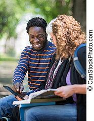 feliz, estudiante, utilizar, tableta de digital, con, amigos, en, campus