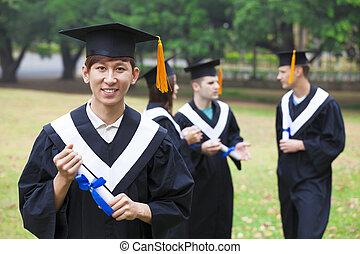 feliz, estudiantes, en, trajes de ceremonia de entrega de diplomas, en, campus de la universidad