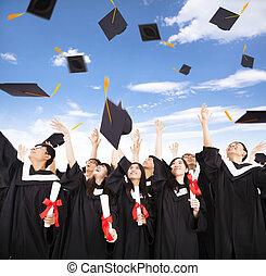 feliz, estudiantes, lanzamiento, casquillos de la graduación, en, el, aire