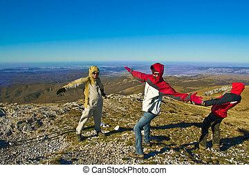 feliz, excursionistas, en, montañas, juego, con, fuerte, viento