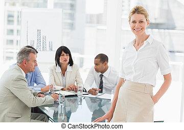 feliz, executiva, olhando câmera, enquanto, pessoal, discuta, atrás de, dela, em, escritório