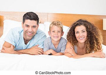 feliz, família jovem, encontrar-se cama, olhando câmera