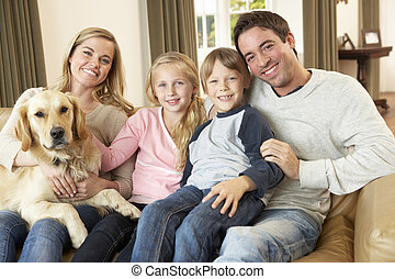 feliz, família jovem, sentar sofá, segurando, um, cão