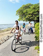 feliz, familia asiática, bicicletas de equitación, en, el, hermoso, mañana, en, el, playa., al aire libre, retrato