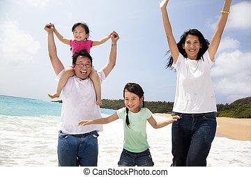 feliz, familia asiática, saltar, en la playa