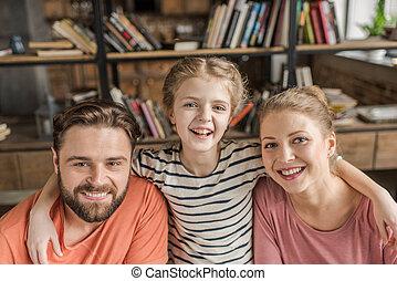 feliz, familia joven, con, un niño, se abrazar, y, sonriente, en cámara del juez