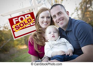 feliz, familia joven, delante de, vendido, signo bienes raíces